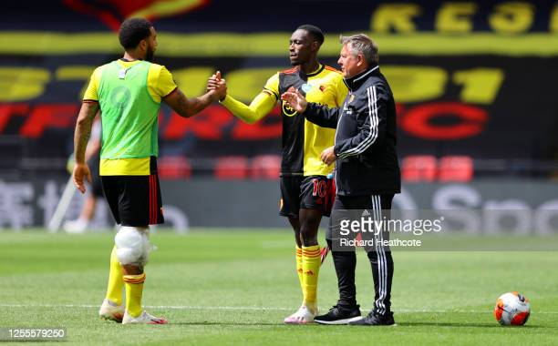 Troy Deeney is challenged by with Danny Welbeck of Watford and Craig Shakespeare Watford assistant manager during the Premier League match between...