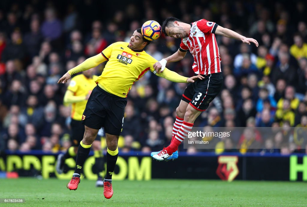 Troy Deeney of Watford (L) and Maya Yoshida of Southampton (R) battle to win a header during the Premier League match between Watford and Southampton at Vicarage Road on March 4, 2017 in Watford, England.