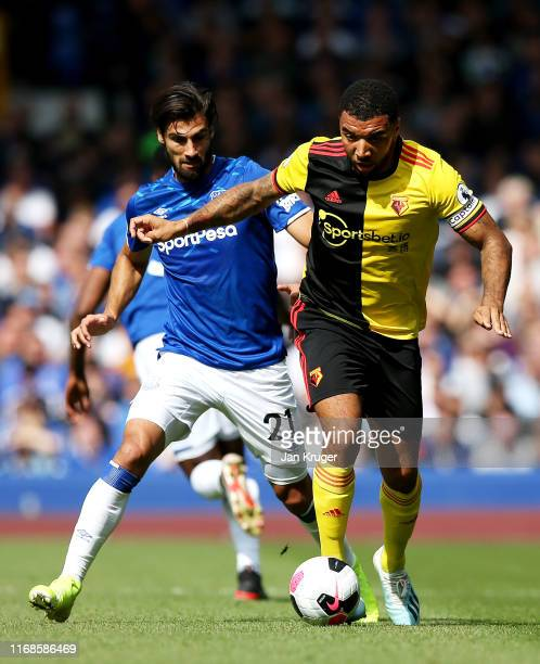 Troy Deeney of Watford battles for possession with Andre Gomes of Everton during the Premier League match between Everton FC and Watford FC at...