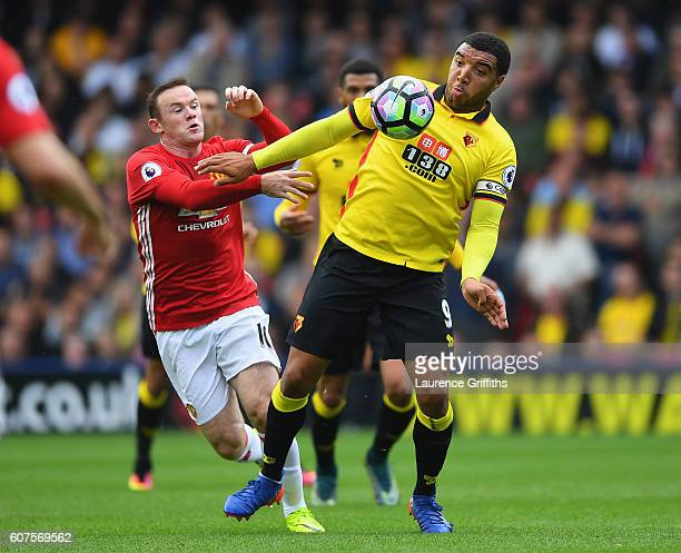 Troy Deeney of Watford battles with Wayne Rooney of Manchester United during the Premier League match between Watford and Manchester United at...