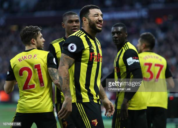 Troy Deeney of Watford celebrates after scoring his team's first goal with his team mates during the Premier League match between West Ham United and...