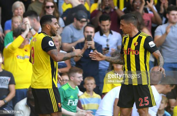 Troy Deeney of Watford celebrates as he scores his team's first goal with Jose Holebas of Watford during the Premier League match between Watford FC...