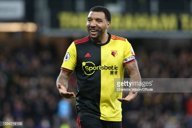 Troy Deeney of Watford celebrates their opening goal during the Premier League match between Watford FC and Liverpool FC at Vicarage Road on February...
