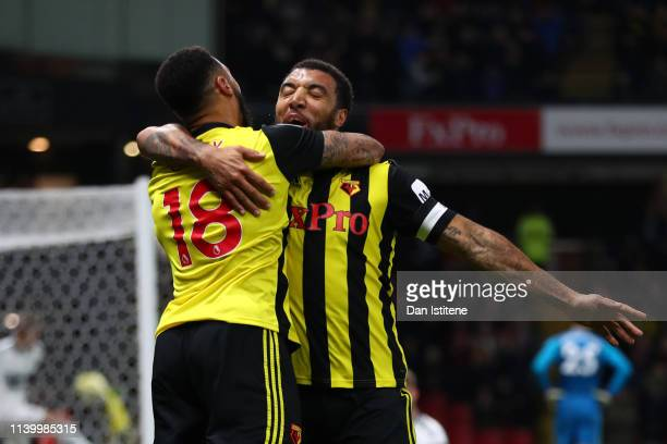 Troy Deeney of Watford celebrates with teammate Andre Gray after scoring his team's third goal during the Premier League match between Watford FC and...