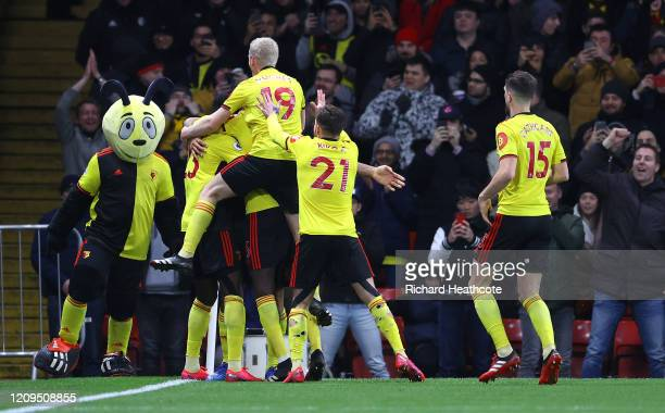 Troy Deeney of Watford celebrates with teammates after scoring his team's third goal during the Premier League match between Watford FC and Liverpool...