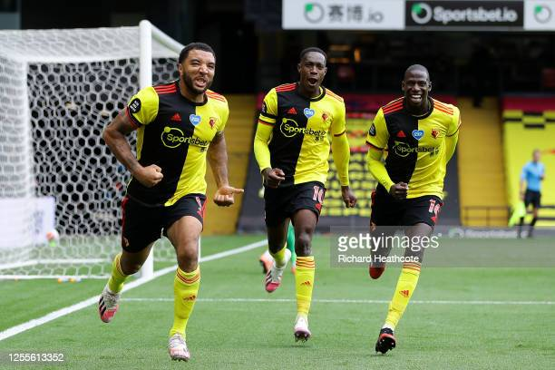 Troy Deeney of Watford celebrates with teammates after scoring his team's second goal from a penalty during the Premier League match between Watford...