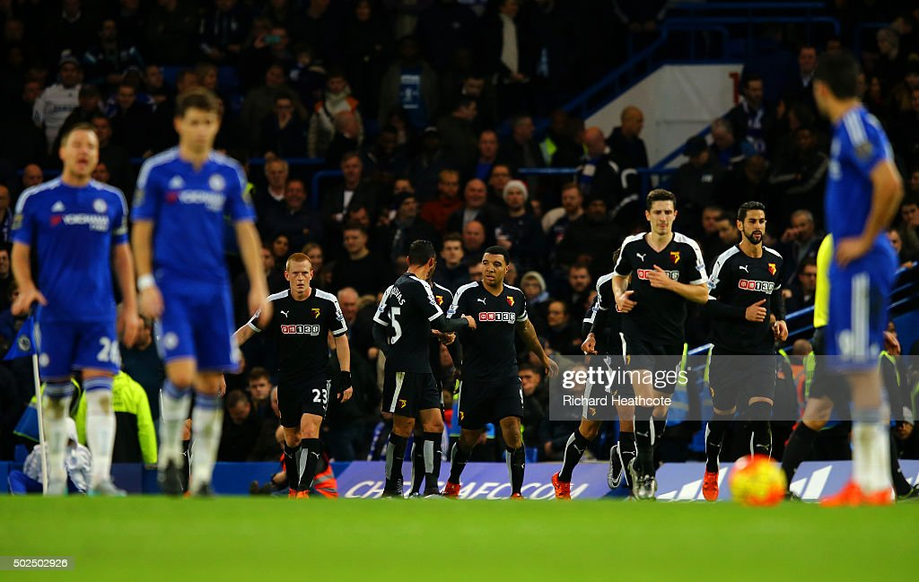 Troy Deeney of Watford celebrates with team-mates after scoring their first goal from the penalty spot as the Chelsea players react during the Barclays Premier League match between Chelsea and Watford at Stamford Bridge on December 26, 2015 in London, England.