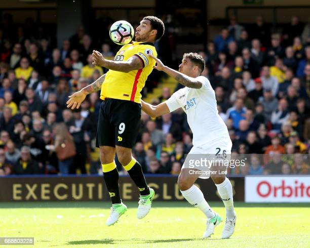 Troy Deeney of Watford controls the ball while under pressure from Kyle Naughton of Swansea City during the Premier League match between Watford and...