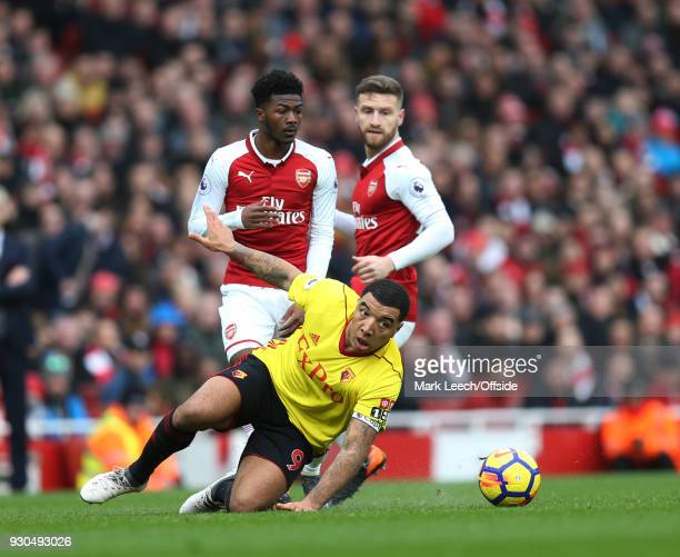 Troy Deeney of Watford falls under pressure from Ainsley MaitlandNiles of Arsenal during the Premier League match between Arsenal and Watford at...