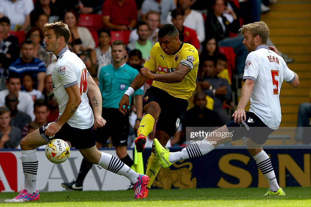Troy Deeney of Watford gets a shot on goal under pressure from Dorian Dervite (l) and Tim Ream (r) of Bolton Wanderers during the Sky Bet Championship match between Watford and Bolton Wanderers at Vicarage Road on August 9, 2014 in Watford, England.