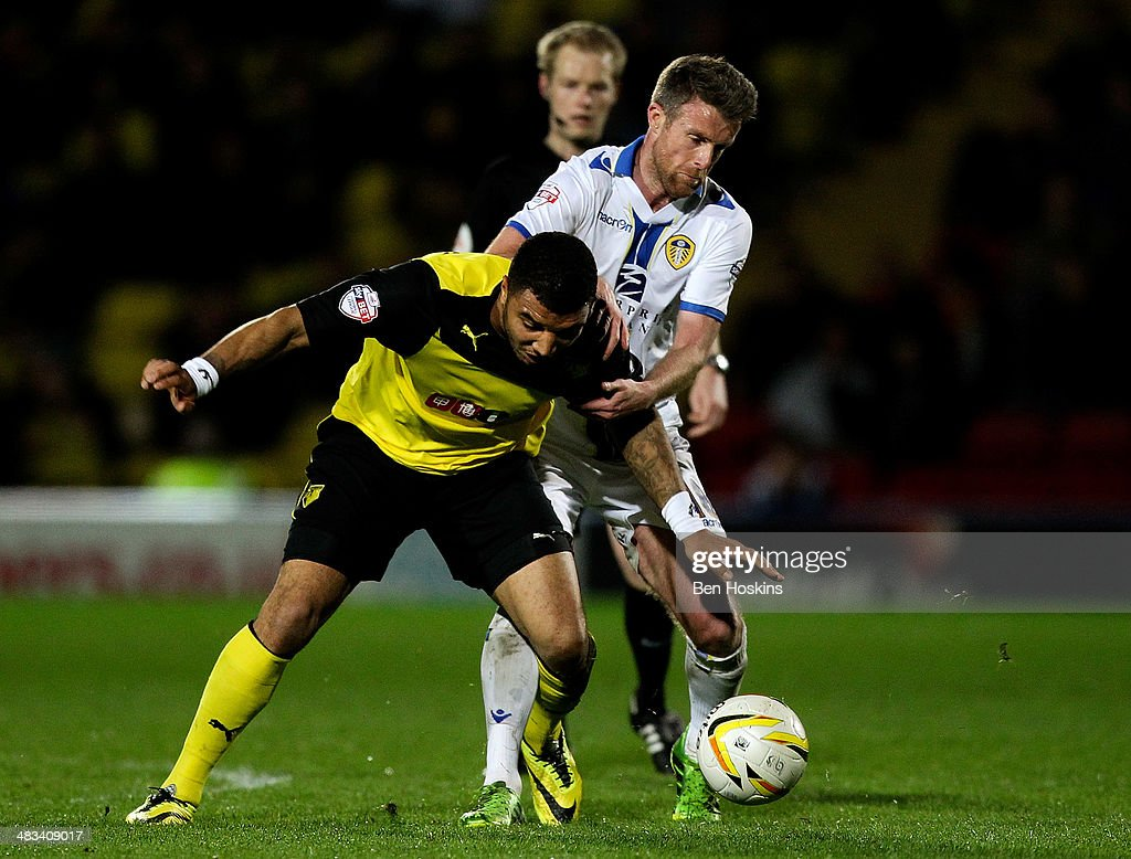Troy Deeney (L) of Watford holds off pressure from Michael Tonge of Leeds during the Sky Bet Championship match between Watford and Leeds United at Vicarage Road on April 8, 2014 in Watford, England.