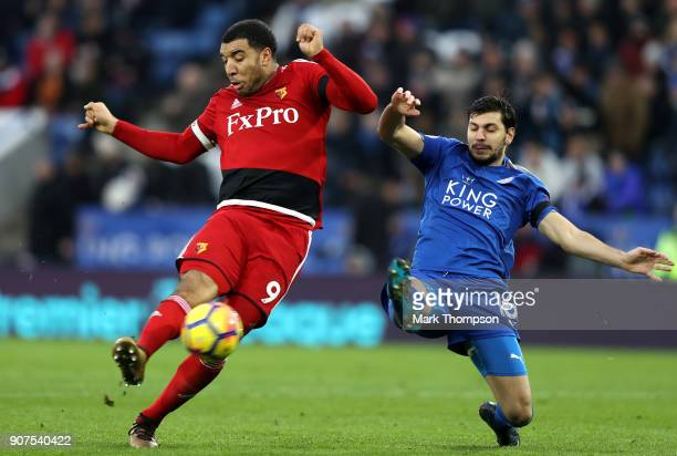 Troy Deeney of Watford is challenged by Aleksander Dragovic of Leicester City during the Premier League match between Leicester City and Watford at...