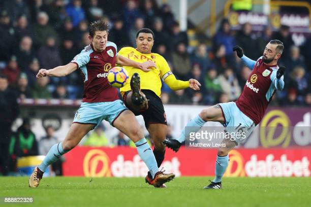 Troy Deeney of Watford is challenged by James Tarkowski of Burnley and Steven Defour of Burnley during the Premier League match between Burnley and...
