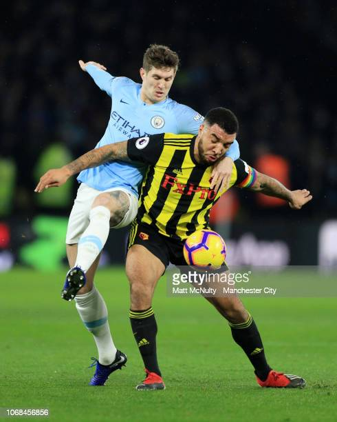 Troy Deeney of Watford is challenged by John Stones of Manchester City during the Premier League match between Watford FC and Manchester City at...
