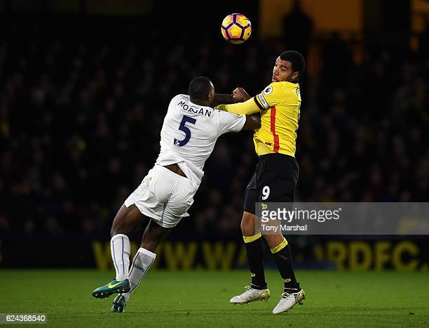 Troy Deeney of Watford is tackled by Wes Morgan of Leicester City during the Premier League match between Watford and Leicester City at Vicarage Road...