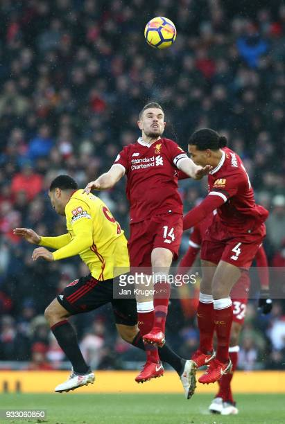 Troy Deeney of Watford Jordan Henderson and Virgil van Dijk of Liverpool jump for the header during the Premier League match between Liverpool and...