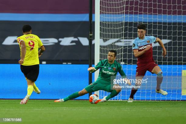 Troy Deeney of Watford scores his team's first goal past Lukasz Fabianski of West Ham United during the Premier League match between West Ham United...