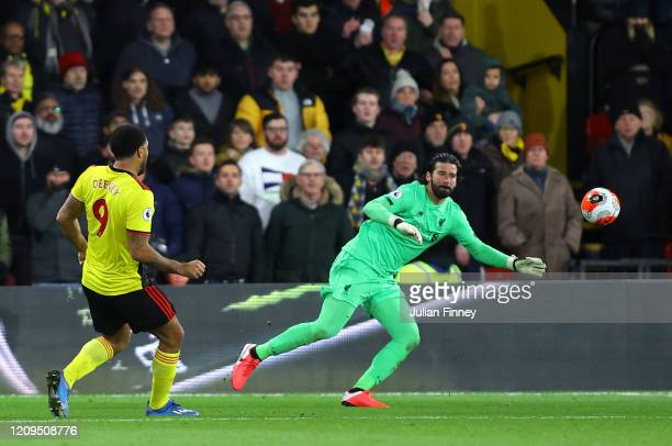 Troy Deeney of Watford scores his team's third goal past Alisson Becker of Liverpool during the Premier League match between Watford FC and Liverpool...