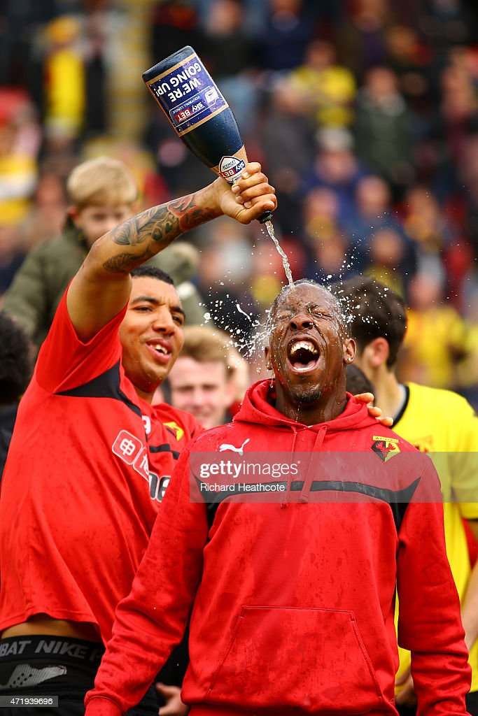 Troy Deeney pours chamagne on Lloyd Doyley as they celebrate promotion to the premier league during the Sky Bet Championship match between Watford and Sheffield Wednesday at Vicarage Road on May 2, 2015 in Watford, England.