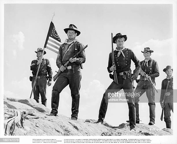Troy Donahue and three unknown actors holding rifles and one unknown actor holding a flag while looking over a rocky cliff in a scene from the film...
