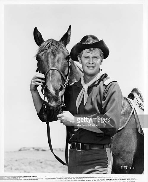 Troy Donahue being affectionate with a horse in a scene from the film 'A Distant Trumpet' 1964