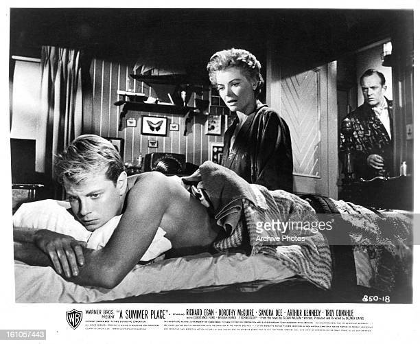 Troy Donahue laying on his stomach in bed looking upset as Dorothy McGuire walks in his room in a scene from the film 'A Summer Place' 1959