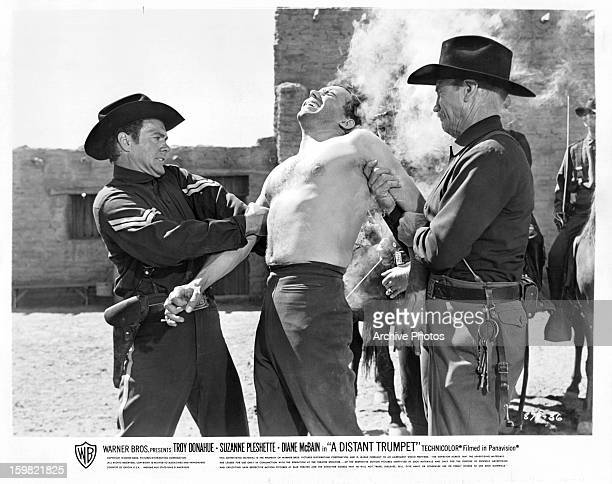 Troy Donahue restrains a man in a scene from the film 'A Distant Trumpet' 1964