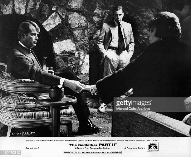 Troy Donahue sits holding the hand of Talia Shire in a scene from the film 'The Godfather Part II' 1974