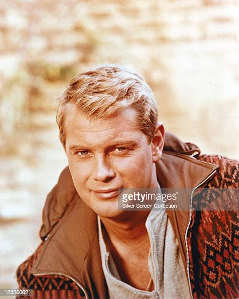 Troy Donahue US actor wearing a grey sweatshirt beneath a brown zipup jacket with a patterned fabric exterior circa 1955