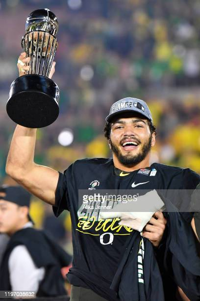 Troy Dye of the Oregon Ducks holds up the Rose Bowl trophy after the game against the Wisconsin Badgers at the Rose Bowl on January 01, 2020 in...