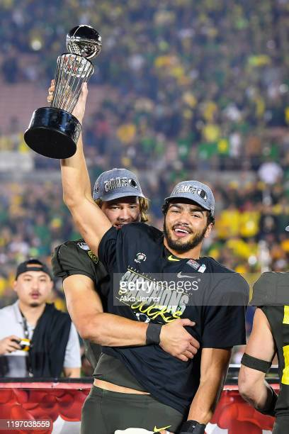 Troy Dye of the Oregon Ducks, right, and Justin Herbert celebrate after the game against the Wisconsin Badgers at the Rose Bowl on January 01, 2020...