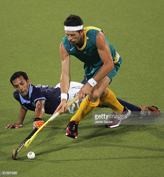 Troy Elder of Australia chases after the ball as Deepak Thakur of India falls to the pitch during the men's field hockey preliminaries on August 19...