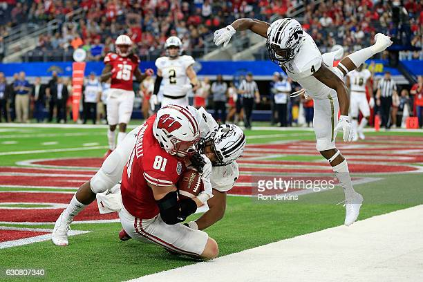 Troy Fumagalli of the Wisconsin Badgers scores a touchdown against Caleb Bailey and Darius Phillips of the Western Michigan Broncos in the fourth...
