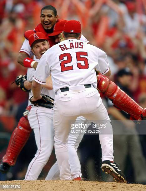 Troy Glaus of the Anaheim Angels runs towards teammates Scott Spiezio and Benjie Molina after the Angels defeated the Minnesota Twins 135 win the...