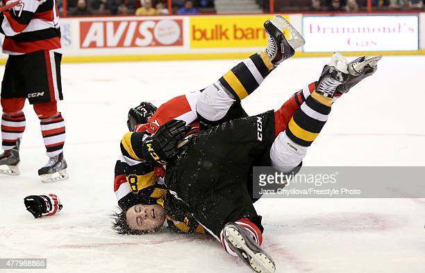 Troy Henley of the Ottawa 67's slams Mack Lemmon of the Kingston Frontenacs onto the ice during a fight during an OHL game at Canadian Tire Centre on...