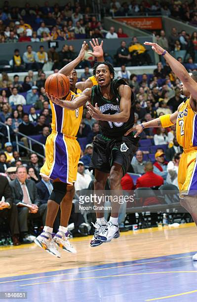 Troy Hudson of the Minnesota Timberwolves drives to the basket between Kobe Bryant and Derek Fisher of the Los Angeles Lakers during the game at...