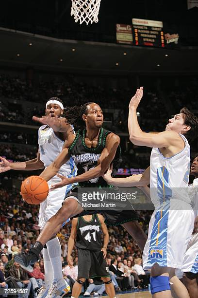 Troy Hudson of the Minnesota Timberwolves goes to the basket against Nene and Eduardo Najera of the Denver Nuggets on November 3 2006 at the Pepsi...
