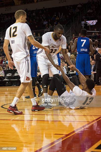 Troy Huff and Nnanna Egwu help Aaron Bowen of the Erie BayHawks up from the court during the game against the Delaware 87ers at the Erie Insurance...