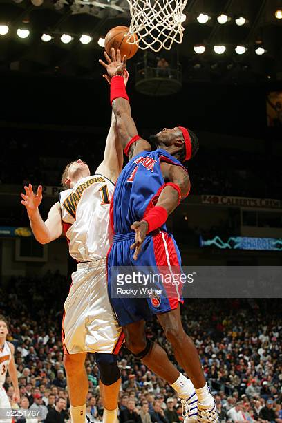 Troy Murphy of the Golden State Warriors rebounds over Ben Wallace of the Detroit Pistons February 27, 2005 at the Arena in Oakland, California. NOTE...