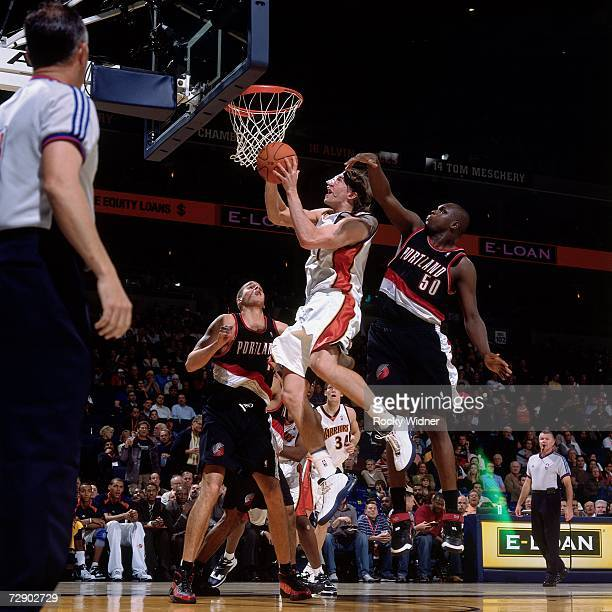 Troy Murphy of the Golden State Warriors takes the ball to the basket against Joel Przybilla and Zach Randolph of the Portland Trail Blazers during a...
