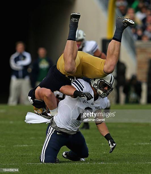 Troy Niklas of the Notre Dame Fighting Irish is hit and flipped by Spencer Hasdley of the BYU Courgars at Notre Dame Stadium on October 20 2012 in...