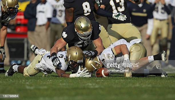Troy Niklas of the Notre Dame Fighting Irish moves to recover a fumble by Marcus Thomas of the Navy Midshipmen as Bo Snelson crashes in at Notre Dame...