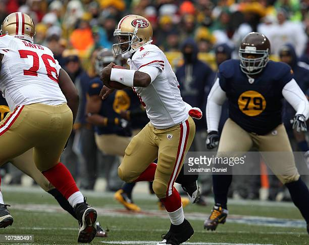 Troy Smith of the San Francisco 49ers runs past teammate Anthony Davis as Ryan Pickett of the Green Bay Packers pursues the play at Lambeau Field on...