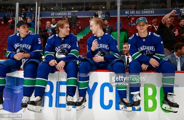 Troy Stecher Brock Boeser Elias Pettersson and Nikolay Goldobin of the Vancouver Canucks sit on the bench during their NHL game against the Calgary...