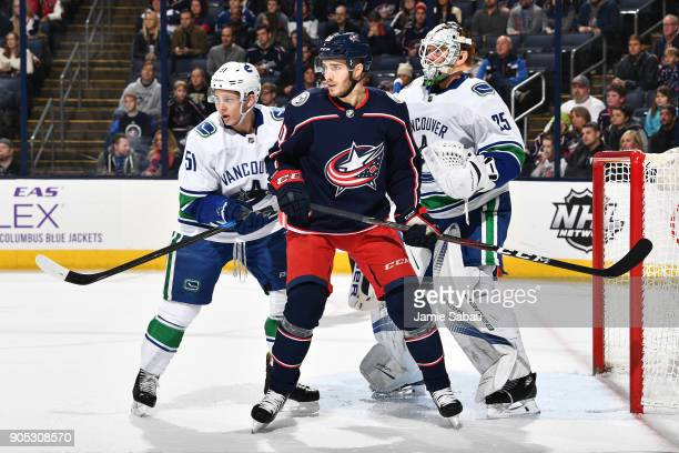 Troy Stecher of the Vancouver Canucks and Alexander Wennberg of the Columbus Blue Jackets battle for position in front of goaltender Jacob Markstrom...
