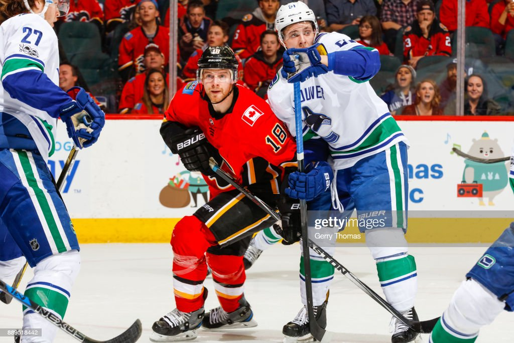 Troy Stecher #51 of the Vancouver Canucks and Matt Stajan #18 of the Calgary Flames battle for position in a NHL game against the Vancouver Canucks at the Scotiabank Saddledome on December 09, 2017 in Calgary, Alberta, Canada.