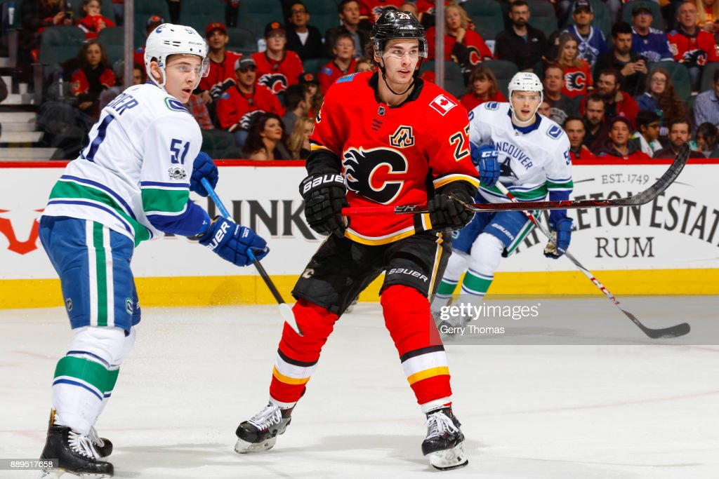 Troy Stecher #51 of the Vancouver Canucks and Sean Monahan #23 of the Calgary Flames in a NHL game against the Vancouver Canucks at the Scotiabank Saddledome on December 09, 2017 in Calgary, Alberta, Canada.