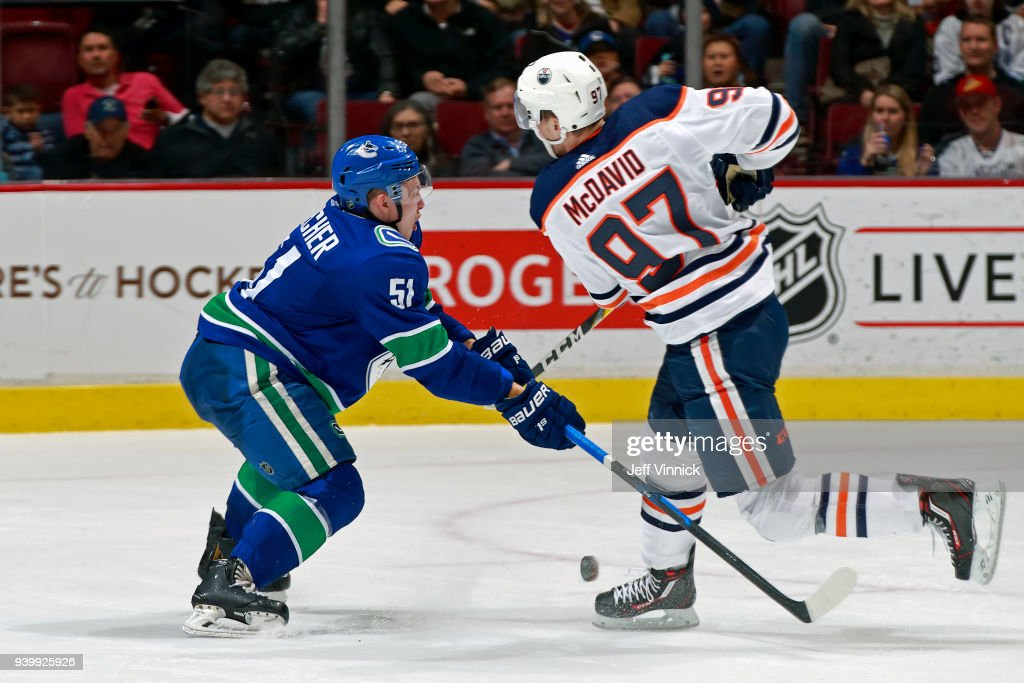 Troy Stecher #51 of the Vancouver Canucks checks Connor McDavid #97 of the Edmonton Oilers during their NHL game at Rogers Arena March 29, 2018 in Vancouver, British Columbia, Canada. Vancouver won 3-1.