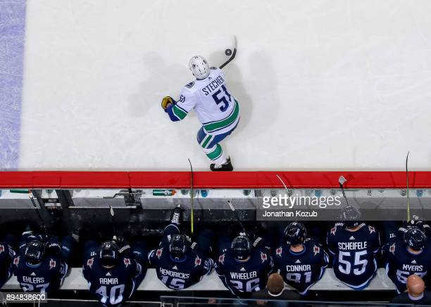 Troy Stecher of the Vancouver Canucks plays the puck as members of the Winnipeg Jets look on from the bench during second period action at the Bell...
