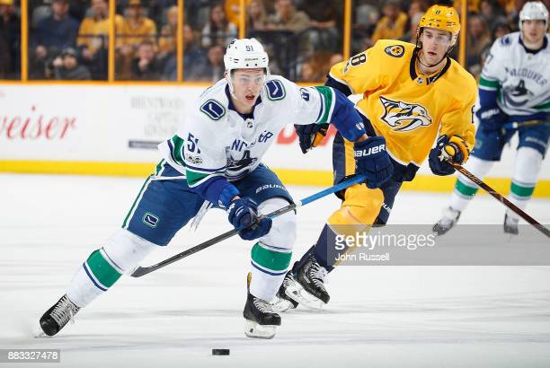 Troy Stecher of the Vancouver Canucks skates against Kyle Turris of the Nashville Predators during an NHL game at Bridgestone Arena on November 30...